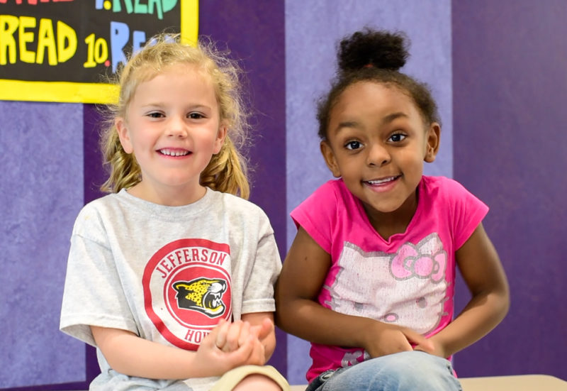Two kindergarten girls giggle as they explain why you should take 2020 survey