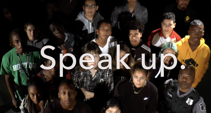 """students looking at camera with words """"speak up"""" across screen"""