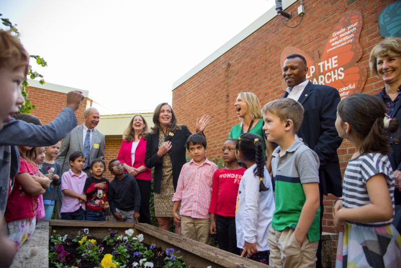 Students and VA First Lady harvest sweet potatoes in school gardent