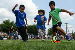 three boys playing soccer
