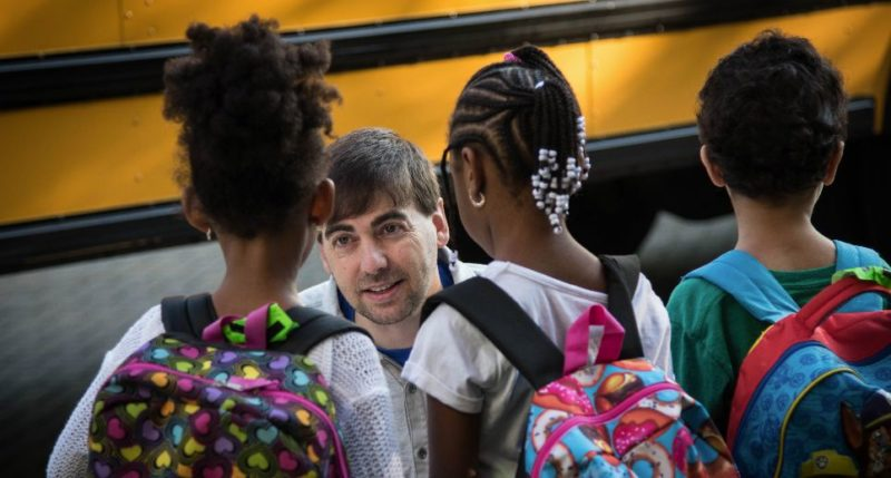 Teacher greeting students on first day of school