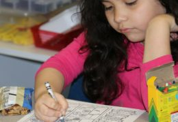 female student coloring at desk
