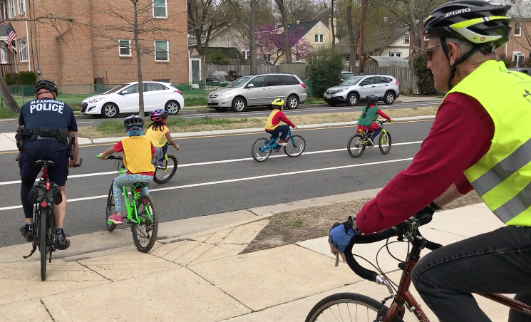 Students riding bikes accompanies by policeman and volunteers