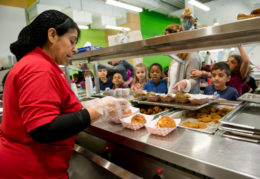 cateria worker serving kids in line