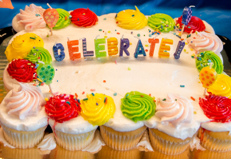 cake surrounded by cupcakes that say celebrate