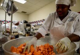 culinary student preparing sweet potatoes in TC kitchen