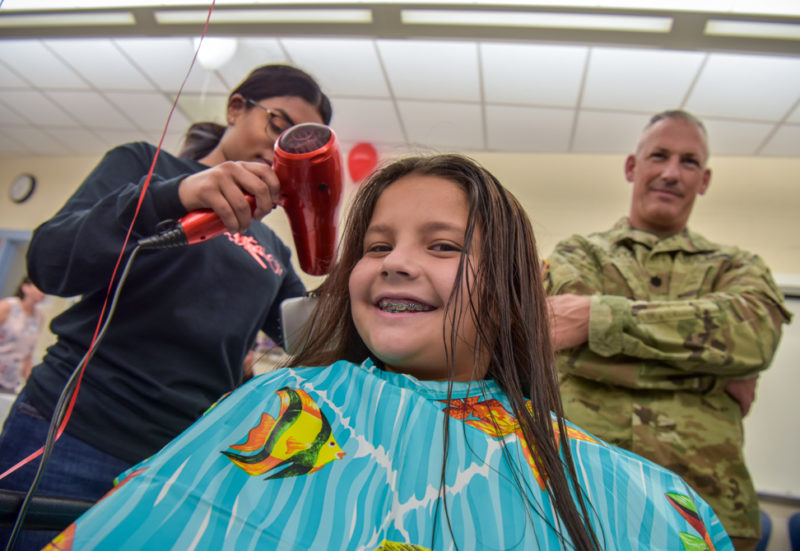 A father watches as a TC Williams cosmetology student dries his daughter's hair