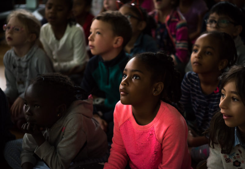 a black female student sits in a crowd of classmates in beautiful light