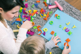 teacher and student working with letters