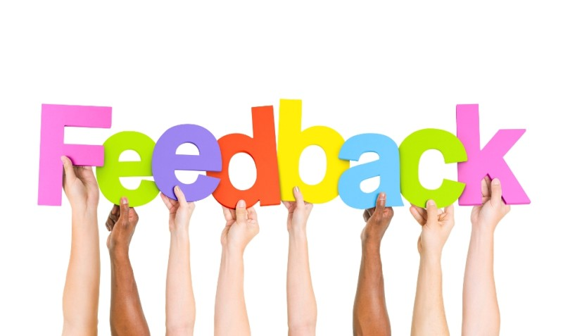 "Hands holding up colorful letters to spell the word ""feedback"""