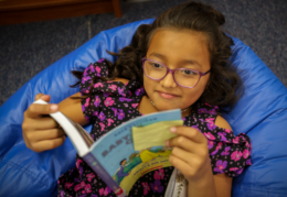 a young girl reads a book on a bean bag in John Adams' library