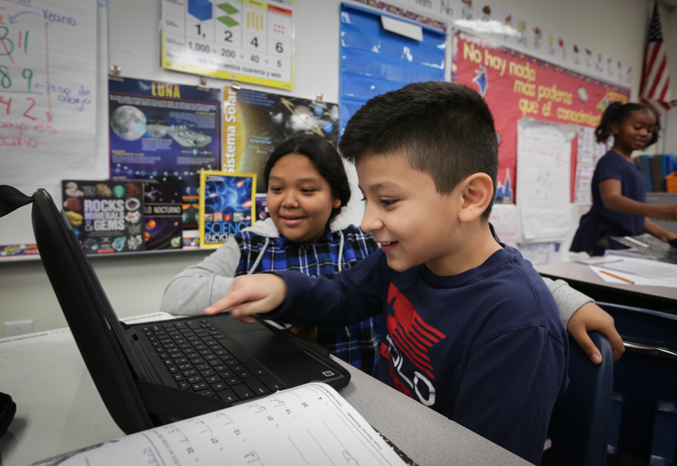two students laughing around a computer