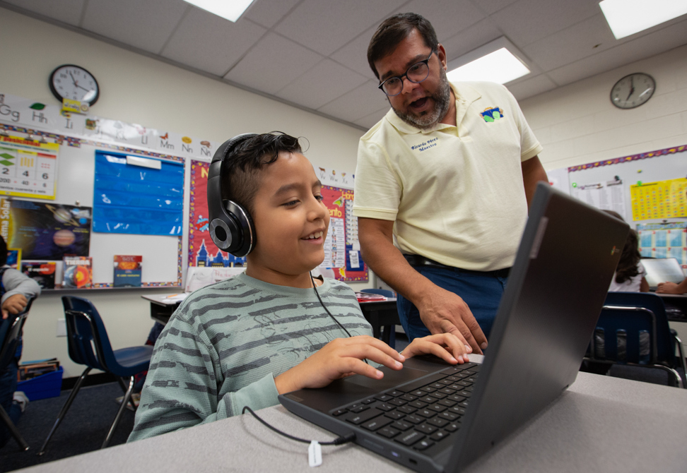 a young boy with headphones working on a computer gets help from his male teacher