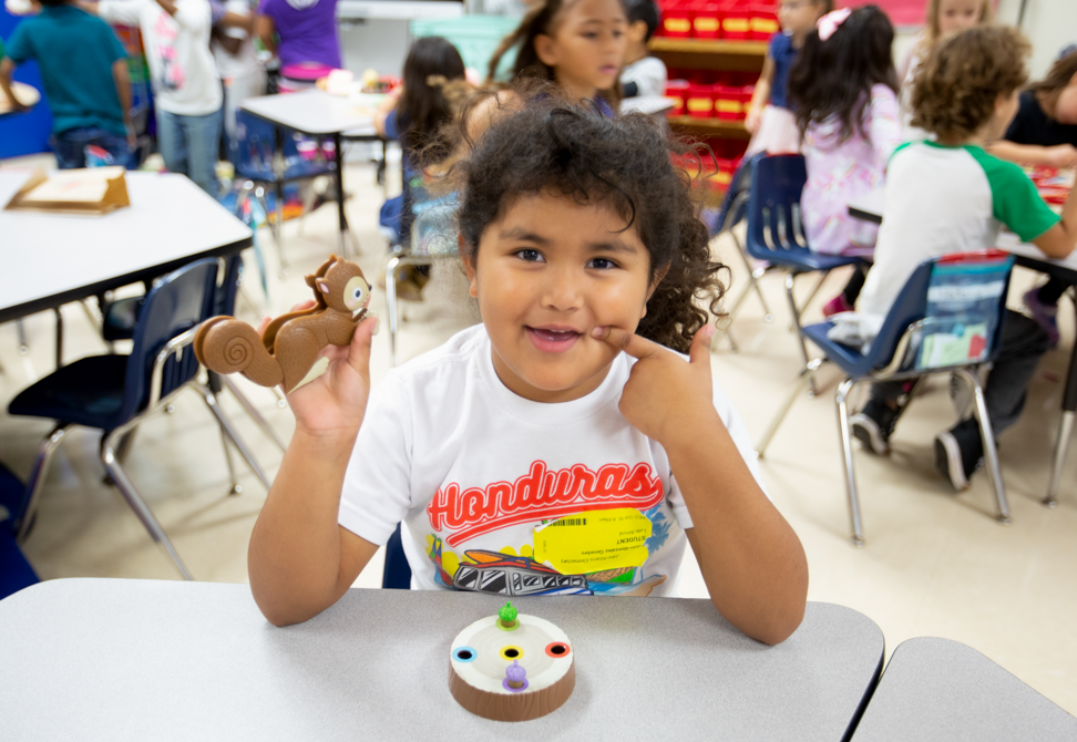 a young girl wearing a Honduras t-shirt holds up a plastic squirrel from a counting game