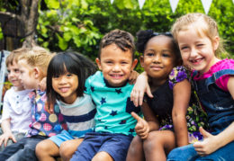 Group of kindergarten kids friends arm around sitting and smilin