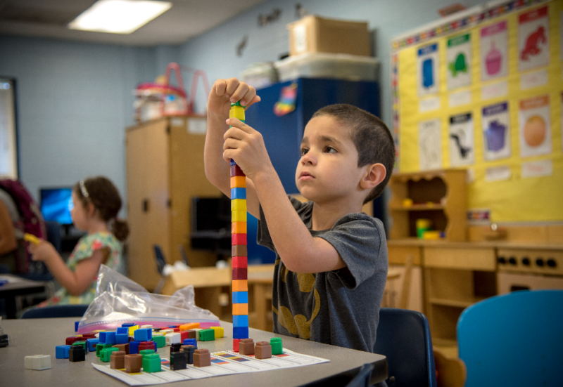 Kindergarten student stacking small colorful blocks on desk