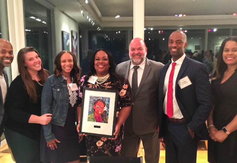 Pierrette Peters stands with her award surrounded by friends and colleagues