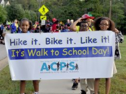 """Students holding """"walk to school"""" banner as they walk to school"""