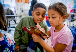 a boy and a girl read a book together about George Washington