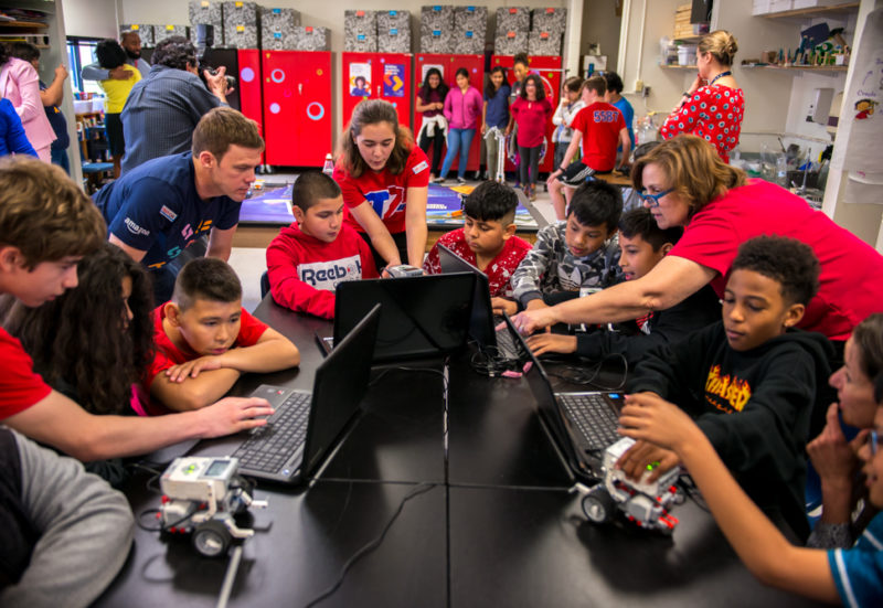 TC Williams High School robotics team students show Cora Kelly fifth graders how their robots are controlled on their laptops