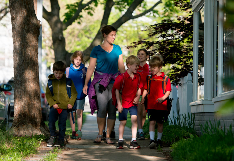 Adult female walking down a sidewalk with a group of students