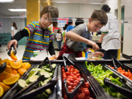 two students serving themselves from the salad bar