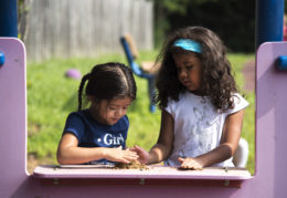 two young girls making mud pies