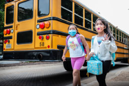 Two girls with masks walk to school after getting off the school bus
