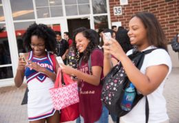 Three high school girls smiling and taking pictures on smartphones