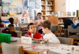 two elementary boys reading book at table