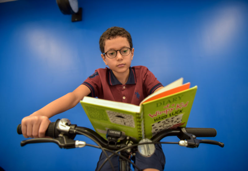 young male student reading a book on stationary bike