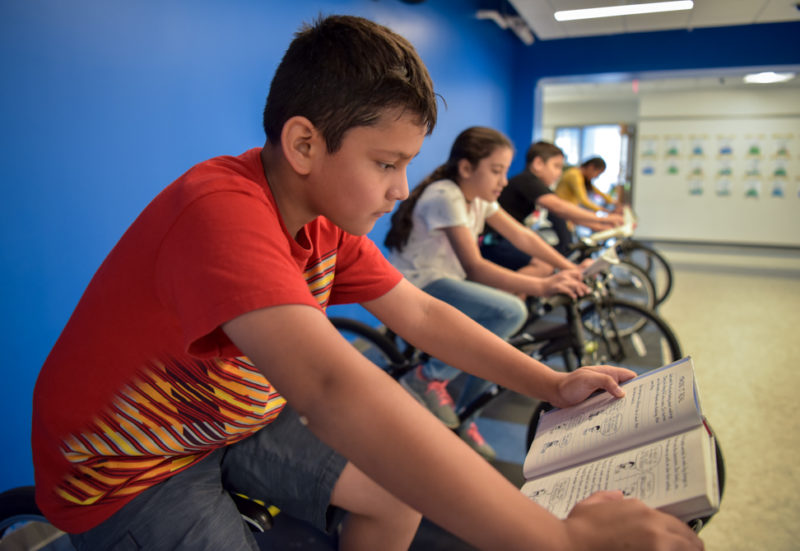 students read on fleet of stationary bikes