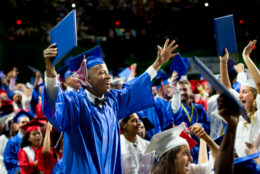 A joyful graduate throws his hands in the air during the ceremony