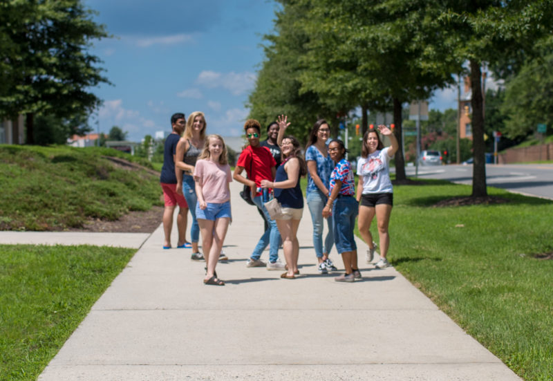 students walking on the sidewalk in front of TC Williams