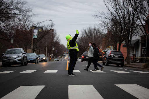 A crossing guard holds up her hand to stop traffic in the center of a crosswalk early in the morning.
