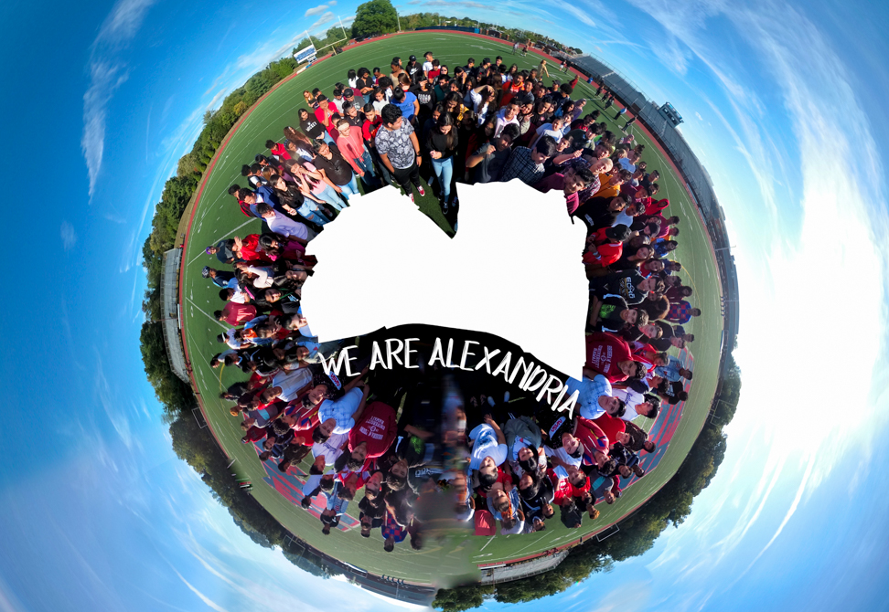 """students on globe with """"We Are Alexandria"""""""