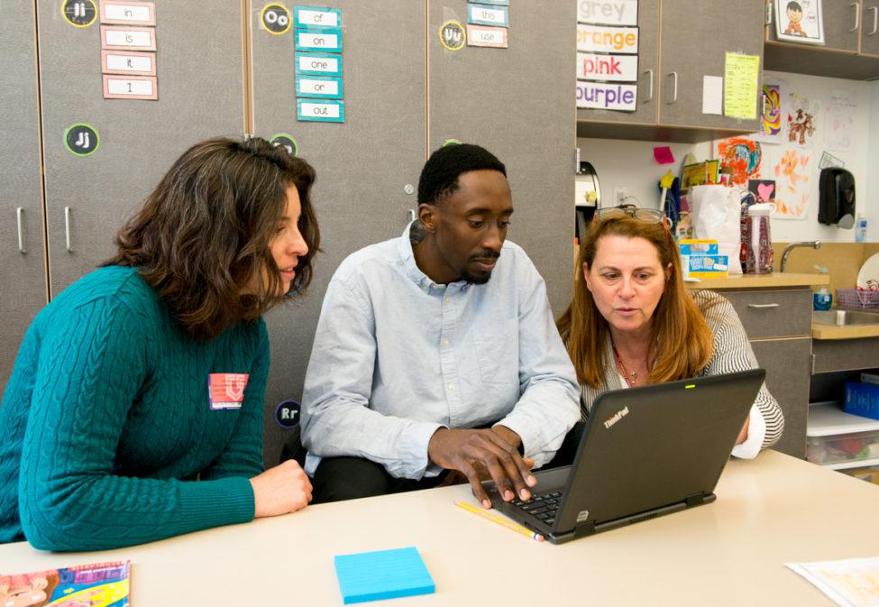 Three teachers gathered around a laptop in classroom