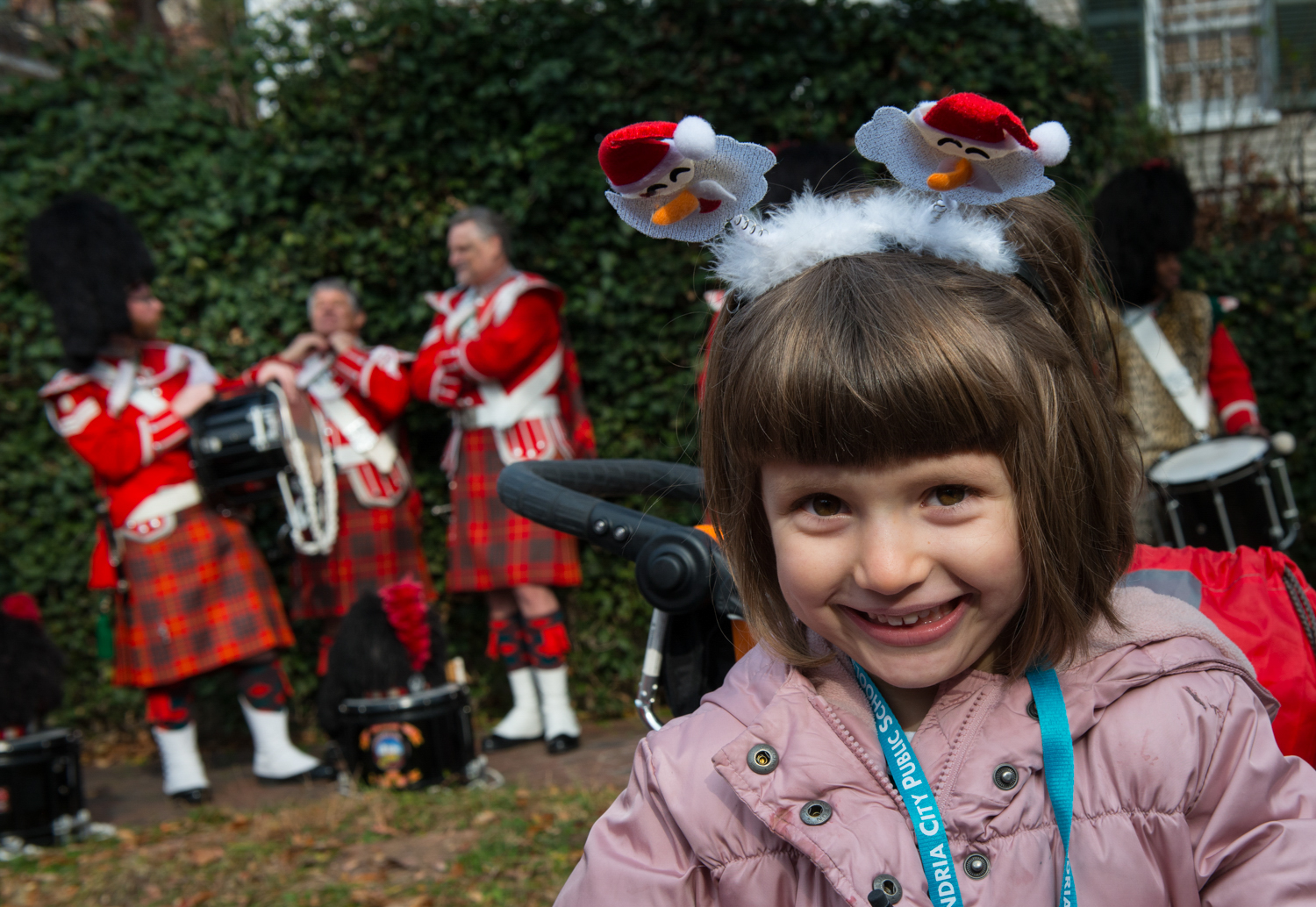 elementary school-age girl with Scottish bagpipe players in the background