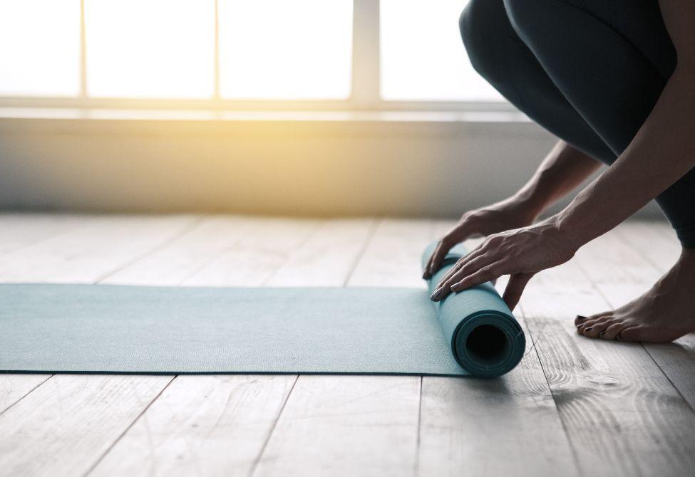 person unrolling yoga mat