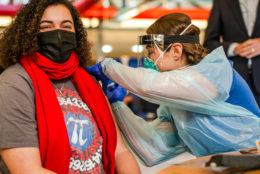 Math teacher Danielle Thorne receives a COVID-19 vaccination shot from a school nurse