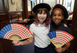 Two elementary school-age girls holding flag fans