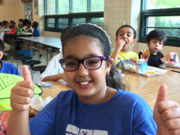 Female Charles Barrett student giving two thumbs up