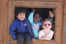 kids peaking out from outdoor play structure