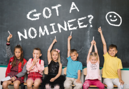 """children sitting in front of chalkboard with words """"got a nominee"""""""