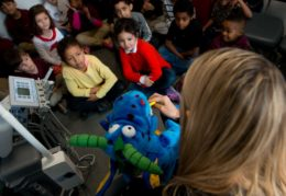 kindergarteners getting lesson in brushing teeth with puppet