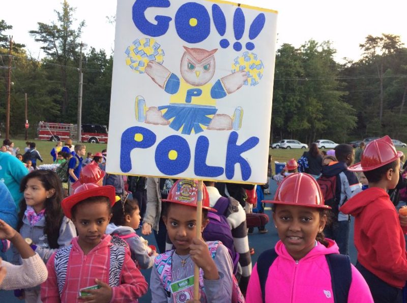 "Pok students on playground. One holding a ""go Polk"" sign"