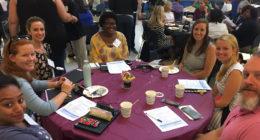New teachers sitting around table at new teacher orientation