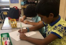 Two male elementary school students working at their desk