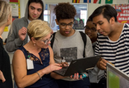 T.C. students looking at teacher's laptop