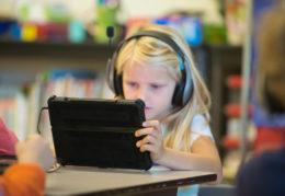 elementary school girl using tablet in classroom